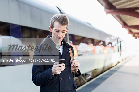 Young businessman using cell phone on railroad station Stock Photo - Premium Royalty-Free, Image code: 698-07611481