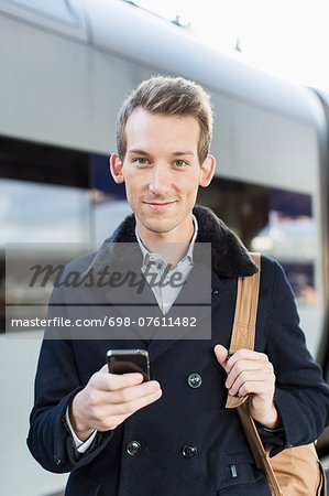 Portrait of confident young businessman holding cell phone on railroad station