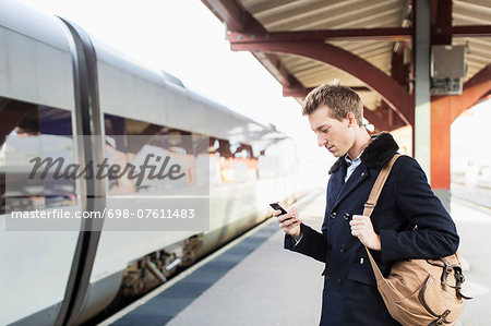 Side view of young businessman using cell phone on railroad station Stock Photo - Premium Royalty-Free, Image code: 698-07611483
