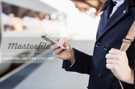 Midsection of businessman using cell phone on railroad station Stock Photo - Premium Royalty-Free, Image code: 698-07611484