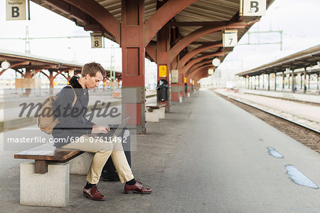 Full length side view of young businessman using laptop on railroad station Stock Photo - Premium Royalty-Free, Image code: 698-07611492
