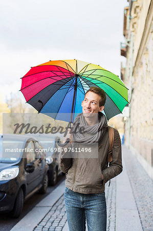 Young businessman with umbrella walking on footpath Stock Photo - Premium Royalty-Free, Image code: 698-07611496