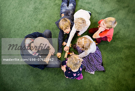 Directly above shot of teacher with students playing on rug in kindergarten Stock Photo - Premium Royalty-Free, Image code: 698-07611542