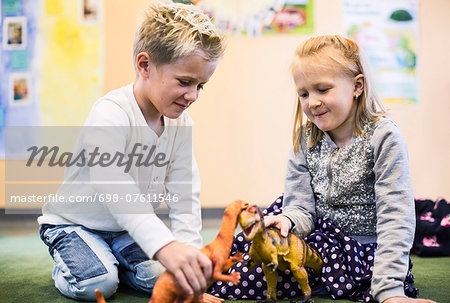 Kids playing with toy dinosaurs in kindergarten Stock Photo - Premium Royalty-Free, Image code: 698-07611546