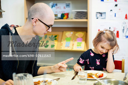 Male teacher scolding girl for not having food in kindergarten Stock Photo - Premium Royalty-Free, Image code: 698-07611563