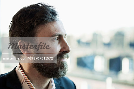 Thoughtful businessman looking away outdoors Stock Photo - Premium Royalty-Free, Image code: 698-07611572