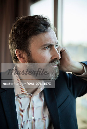 Thoughtful businessman leaning on window in hotel Stock Photo - Premium Royalty-Free, Image code: 698-07611573