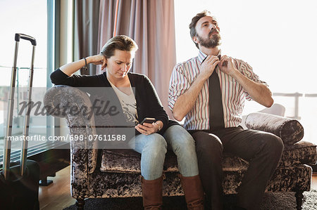 Business couple relaxing on chaise longue in hotel room Stock Photo - Premium Royalty-Free, Image code: 698-07611588