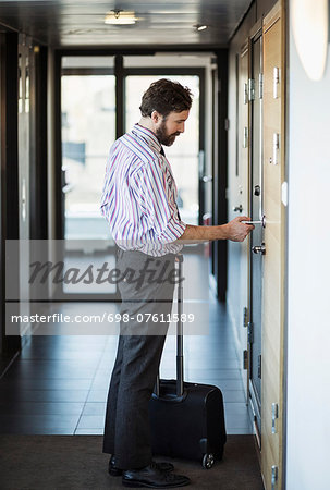 Side view of businessman opening hotel door with cardkey Stock Photo - Premium Royalty-Free, Image code: 698-07611589
