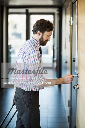 Businessman opening hotel door with cardkey Stock Photo - Premium Royalty-Free, Image code: 698-07611590