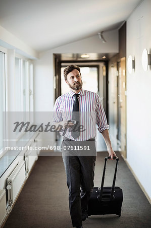 Businessman with suitcase walking in hotel corridor Stock Photo - Premium Royalty-Free, Image code: 698-07611591