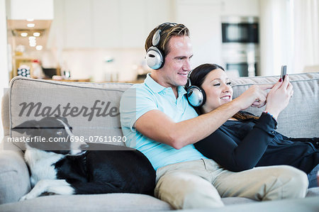 Couple listening to headphones with dog sitting on sofa Stock Photo - Premium Royalty-Free, Image code: 698-07611620