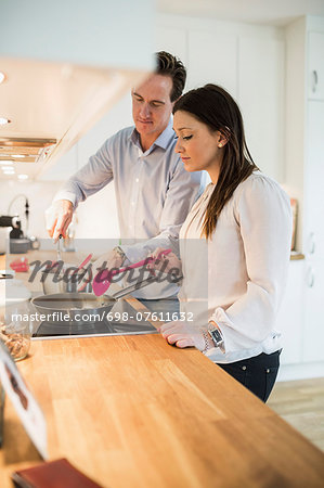 Couple cooking together in kitchen Stock Photo - Premium Royalty-Free, Image code: 698-07611632
