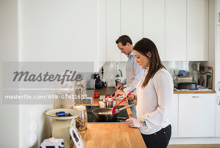 Couple preparing food together in kitchen Stock Photo - Premium Royalty-Free, Image code: 698-07611633