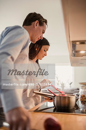 Couple preparing food in domestic kitchen Stock Photo - Premium Royalty-Free, Image code: 698-07611634