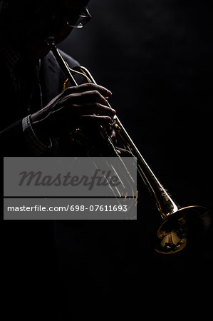 Musician playing trumpet over black background Stock Photo - Premium Royalty-Free, Image code: 698-07611693