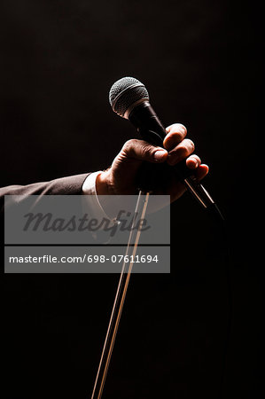 Hand holding microphone over black background Stock Photo - Premium Royalty-Free, Image code: 698-07611694