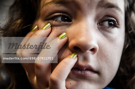 Close-up of pensive girl with hand on chin Stock Photo - Premium Royalty-Free, Image code: 698-07611701