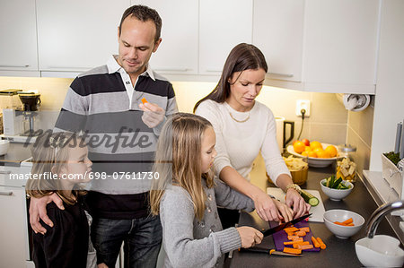 Family cutting vegetables at kitchen counter Stock Photo - Premium Royalty-Free, Image code: 698-07611730