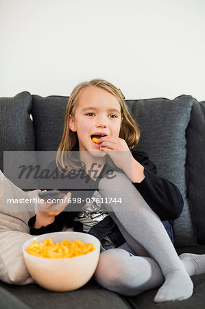 Girl eating snacks while watching TV on sofa at home Stock Photo - Premium Royalty-Free, Image code: 698-07611744