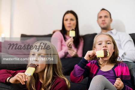 Family eating ice cream in living room Stock Photo - Premium Royalty-Free, Image code: 698-07611756