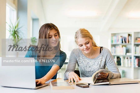 Teenage girls reading book while using laptop at table in school library Stock Photo - Premium Royalty-Free, Image code: 698-07611776