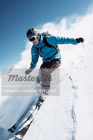 Full length of man skiing on mountain slope Stock Photo - Premium Royalty-Free, Image code: 698-07611800
