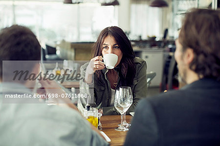Mature woman drinking coffee while looking at colleague during lunch meeting in restaurant Stock Photo - Premium Royalty-Free, Image code: 698-07611868