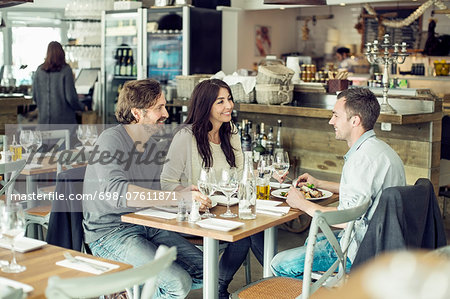Happy friends discussing at table in restaurant