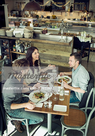 Happy friends communicating in restaurant Stock Photo - Premium Royalty-Free, Image code: 698-07611872