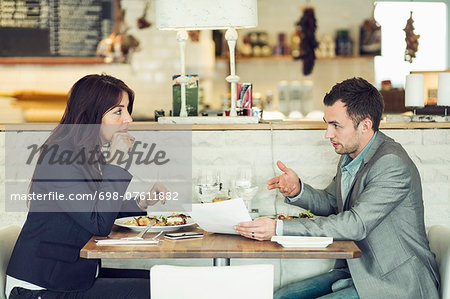 Side view of businessman with female colleague discussing paperwork at restaurant table Stock Photo - Premium Royalty-Free, Image code: 698-07611882