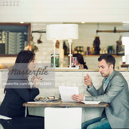 Side view of businessman with female colleague discussing at restaurant table Stock Photo - Premium Royalty-Free, Image code: 698-07611883