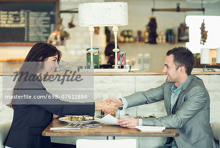 Side view of businessman and businesswoman shaking hands at restaurant table Stock Photo - Premium Royalty-Free, Image code: 698-07611884