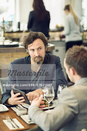 Mature businessman discussing over digital tablet with colleague at restaurant table Stock Photo - Premium Royalty-Free, Image code: 698-07611887