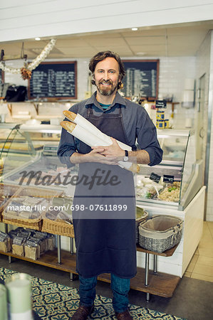 Portrait of mature male baker holding loaves of bread in supermarket Stock Photo - Premium Royalty-Free, Image code: 698-07611899