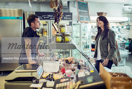 Side view of salesman attending female customer in supermarket Stock Photo - Premium Royalty-Free, Image code: 698-07611903
