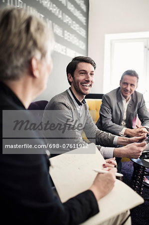 Happy businessman sitting with colleagues at lobby Stock Photo - Premium Royalty-Free, Image code: 698-07611912