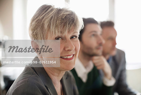 Portrait of happy businesswoman with colleagues in background at office Stock Photo - Premium Royalty-Free, Image code: 698-07611954