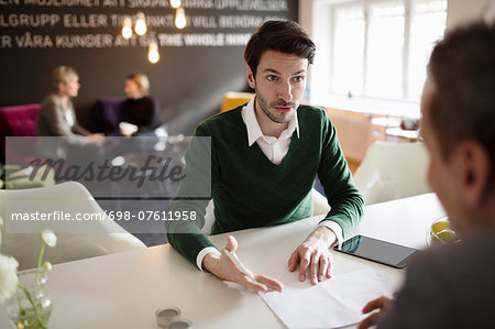 Serious businessman discussing with colleague at office desk Stock Photo - Premium Royalty-Free, Image code: 698-07611958