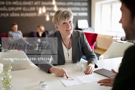 Senior businesswoman discussing with male colleague at office desk