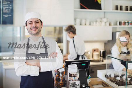 Portrait of confident owner standing arms crossed in cafe Stock Photo - Premium Royalty-Free, Image code: 698-07611968