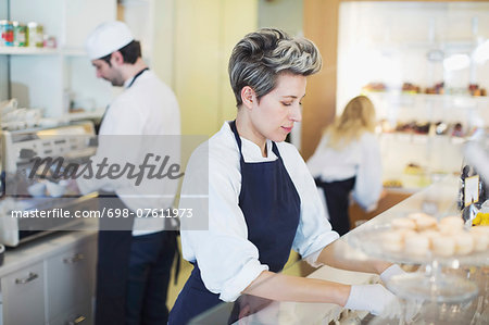 Mid adult female worker working at cafe Stock Photo - Premium Royalty-Free, Image code: 698-07611973