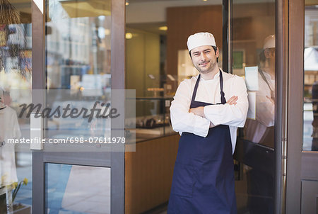 Portrait of confident owner standing with arms crossed at cafe entrance Stock Photo - Premium Royalty-Free, Image code: 698-07611978