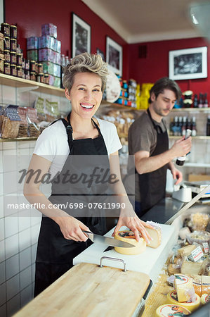 Portrait of happy saleswoman cutting cheese at counter in supermarket Stock Photo - Premium Royalty-Free, Image code: 698-07611990