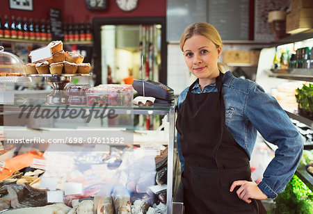 Portrait of confident saleswoman standing by display cabinet in supermarket Stock Photo - Premium Royalty-Free, Image code: 698-07611992