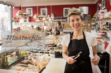 Portrait of happy saleswoman cutting cheese at counter in supermarket Stock Photo - Premium Royalty-Free, Image code: 698-07611996