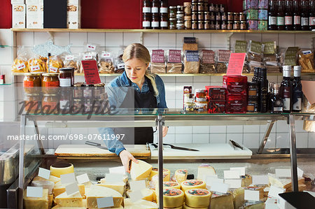 Saleswoman working at display cabinet in supermarket Stock Photo - Premium Royalty-Free, Image code: 698-07611997