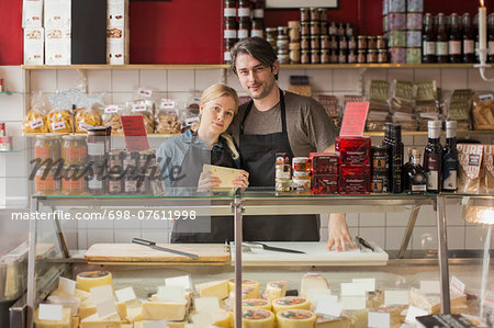 Portrait of male and female worker standing at display cabinet in supermarket Stock Photo - Premium Royalty-Free, Image code: 698-07611998