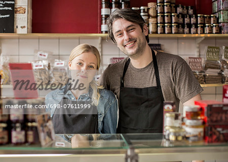 Portrait of smiling worker standing in supermarket Stock Photo - Premium Royalty-Free, Image code: 698-07611999