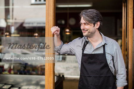 Thoughtful salesman looking away at supermarket entrance Stock Photo - Premium Royalty-Free, Image code: 698-07612005